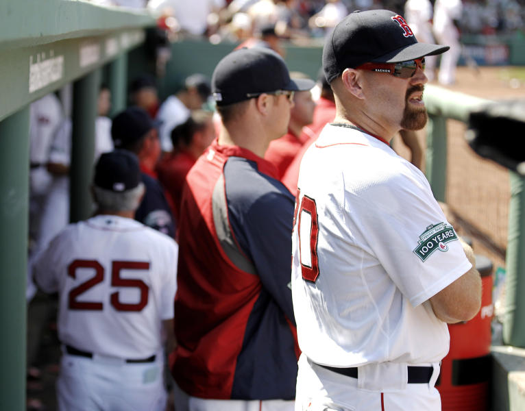 Boston Red Sox's Kevin Youkilis looks out of the dugout as Boston Red Sox manager Bobby Valentine (25) walks away during Boston's 1-0 loss to the Tampa Bay Rays in a baseball game at Fenway Park in Boston Monday, April 16, 2012. Valentine questioned Youkilis' commitment to the game in his weekly television interview, then apologized to the Boston third baseman on Monday. (AP Photo/Winslow Townson)
