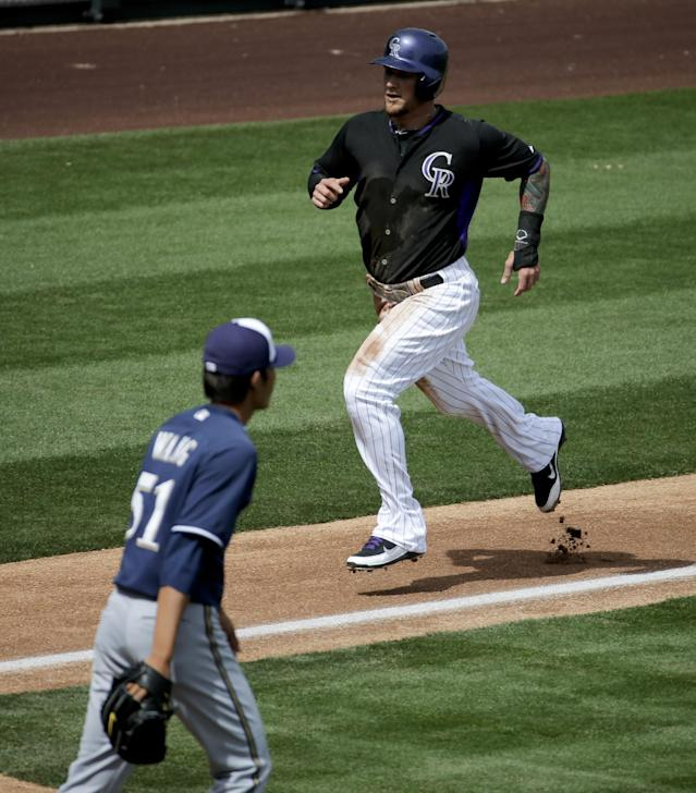 Colorado Rockies' Brandon Barnes scores past Milwaukee Brewers starting pitcher Wei-Chung Wang on a base hit by Michael Cuddyer during the XX inning of a spring exhibition baseball game in Scottsdale, Ariz., Thursday, March 20, 2014. (AP Photo/Chris Carlson)