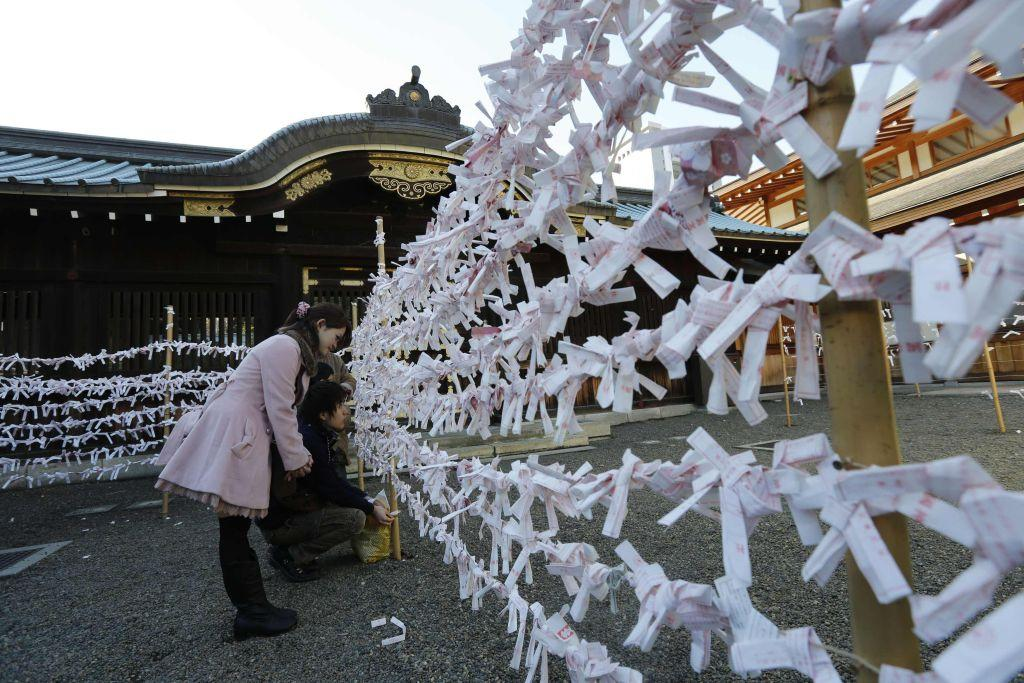 Well-wishers hang new year fortune blessing papers after offering New Year prayers at the Yasukuni Shrine in Tokyo January 1, 2013. Millions of well-wishers visited temples and shrines to offer prayers on the first day of the New Year.