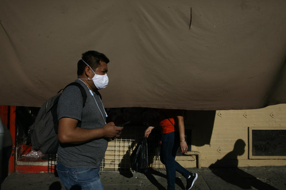 A man with a mask walks on a sidewalk past street vendors during the coronavirus pandemic in the Westlake neighborhood of Los Angeles, Thursday, May 21, 2020. While most of California is welcoming a slight return toward normal this holiday weekend, Los Angeles will not be joining the party. (AP Photo/Jae C. Hong)