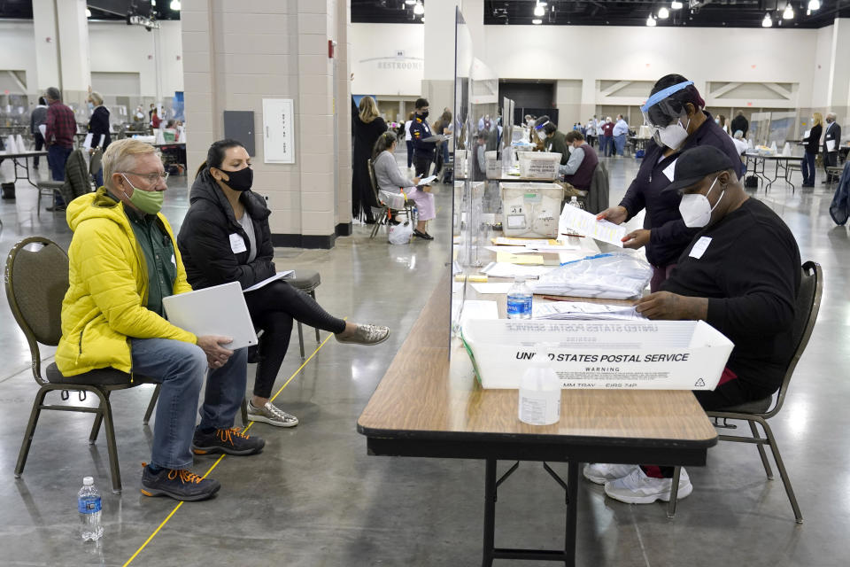 FILE - In this Nov. 20, 2020, file photo, election workers, right, verify ballots as recount observers, left, watch during a Milwaukee hand recount of presidential votes at the Wisconsin Center in Milwaukee. President Donald Trump filed a lawsuit Tuesday, Dec. 1, 2020, in Wisconsin seeking to disqualify hundreds of thousands of ballots in a longshot attempt to overturn Democrat Joe Biden's win in the battleground state he lost by nearly 20,700 votes. (AP Photo/Nam Y. Huh File)
