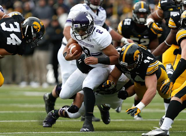 Iowa linebacker James Morris (44) hits Northwestern quarterback Kain Colter (2) during the first half of an NCAA college football game on Saturday, Oct. 26, 2013, in Iowa City, Iowa. (AP Photo/Brian Ray)