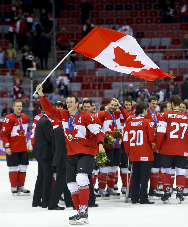 Canada forward Jonathan Toews waves the Canadian flag after Canada beat Sweden 3-0 in the men's gold medal ice hockey game at the 2014 Winter Olympics, Sunday, Feb. 23, 2014, in Sochi, Russia. (AP Photo/Matt Slocum)