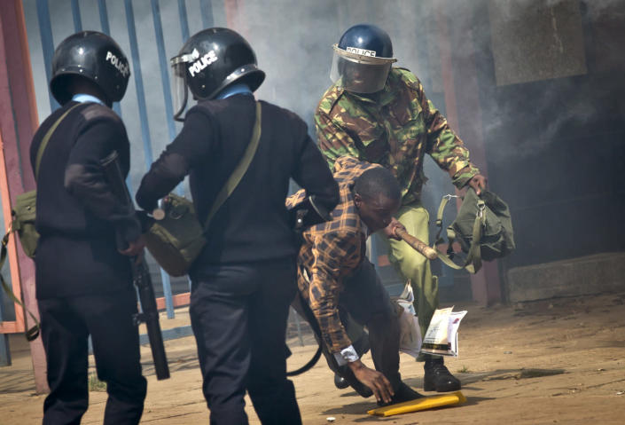 An opposition supporter is beaten with a wooden club by riot police as he tries to flee during a protest in downtown Nairobi, Kenya, May 16, 2016. Kenyan police have tear-gassed and beaten opposition supporters during a protest demanding the disbandment of the electoral authority over alleged bias and corruption. (AP Photo/Ben Curtis)