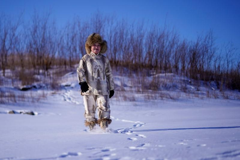 You Wenfeng, 68, an ethnic Hezhen woman, poses with her fishskin clothes at a frozen river in Tongjiang