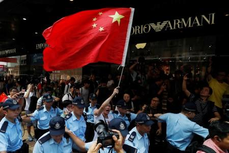 A pro-China supporter is escorted out of a shopping mall by police after waving the national flag of China, at Harbour City in Hong Kong