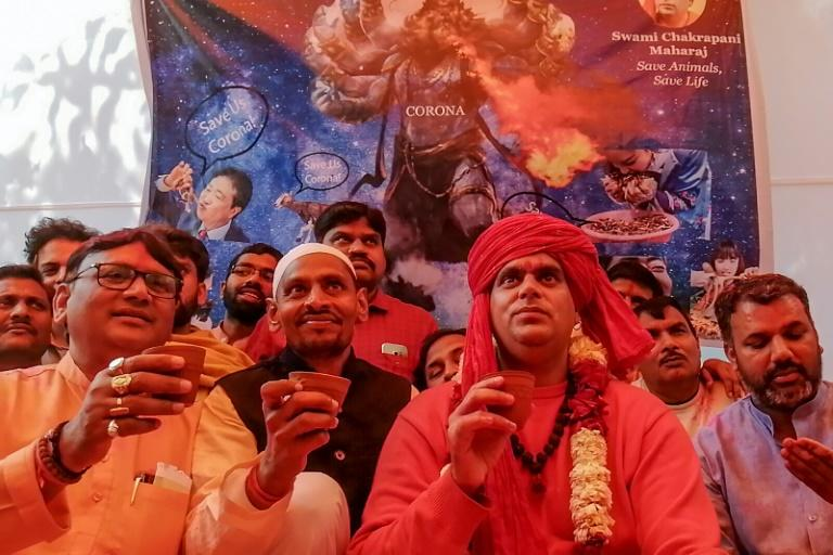 Members of All India Hindu Mahasabha staged fire rituals and drank cow urine in New Delhi Saturday to fight COVID-19