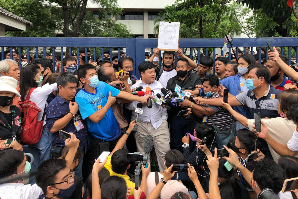 "Protest leader Parit ""Penguin"" Chiwarak, center, is surrounded by journalists outside the criminal court after he was released on bail Saturday, Aug. 15, 2020 in Bangkok, Thailand. Parit was arrested by police Friday on a sedition charge in connection with a July 18 protest. (AP Photo/Busaba Sivasomboon)"