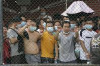 Residents wait in line for the coronavirus test in a district in Guangzhou in southern China's Guangdong province on Sunday, May 30, 2021. The southern Chinese city of Guangzhou shut down a neighborhood and ordered residents to stay home Saturday to be tested for the coronavirus following an upsurge in infections that has rattled authorities. (AP Photo)