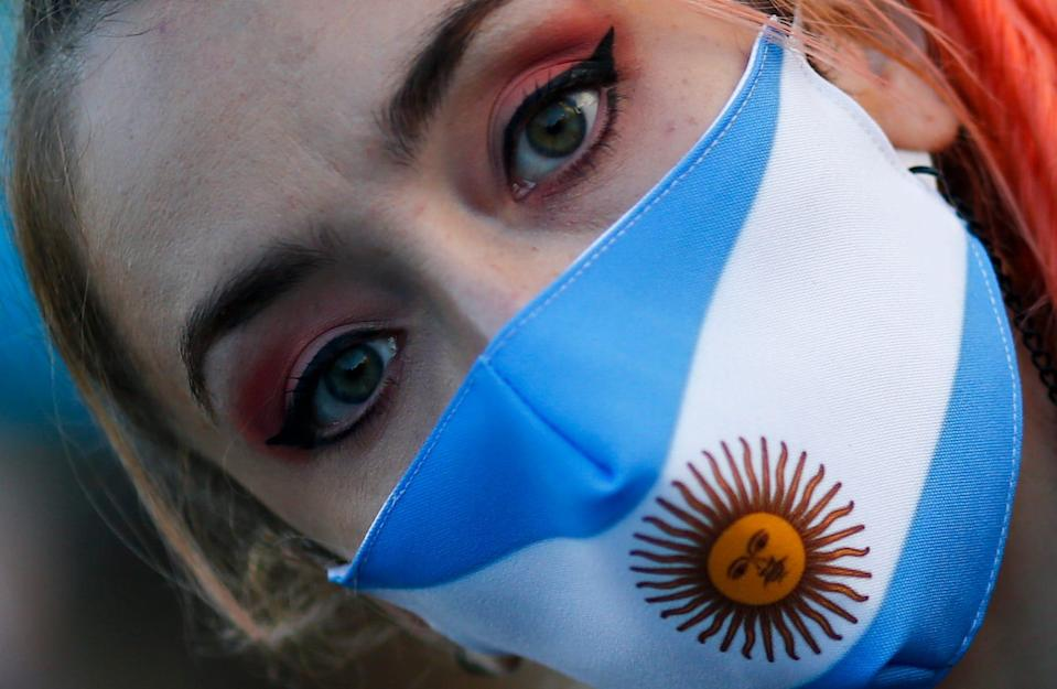 A woman wears a face mask with the colors of the Argentine flag colors during a protest against how the government of President Alberto Fernandez is handling of the new coronavirus pandemic crisis, in Buenos Aires,  on May 25.