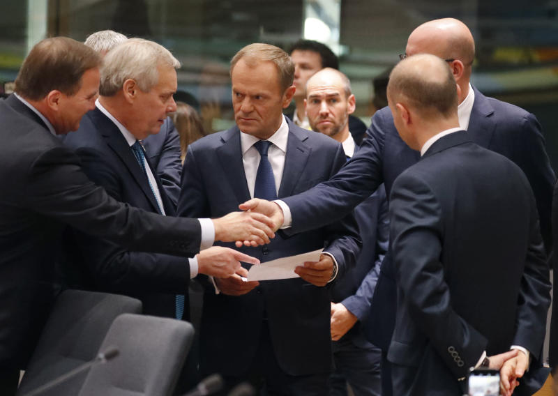 European Council President Donald Tusk, center, speaks with Finnish Prime Minister Antti Rinne, second left, and Belgian Prime Minister Charles Michel, second right, during a round table meeting at EU summit in Brussels, Friday, Oct. 18, 2019. After agreeing on terms for a new Brexit deal, European Union leaders are meeting again to discuss other thorny issues including the bloc's budget and climate change. (AP Photo/Frank Augstein)