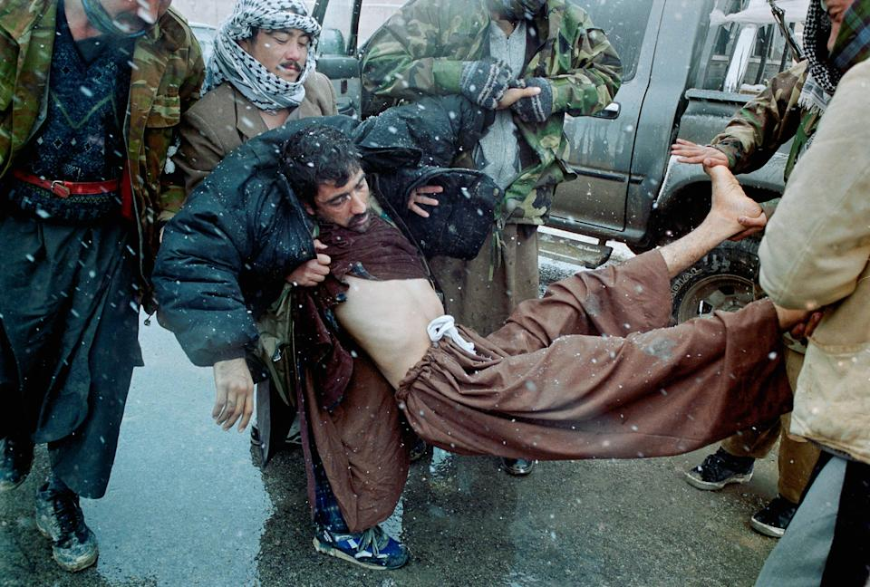 A wounded soldier is carried by two others.