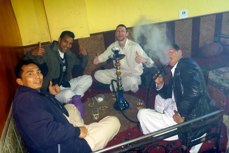 Irish tourist Jonny Blair (C-R) drinks tea and smokes shisha with three Afghan companions in Mazar-i-Sharif during his travels in Afghanistan