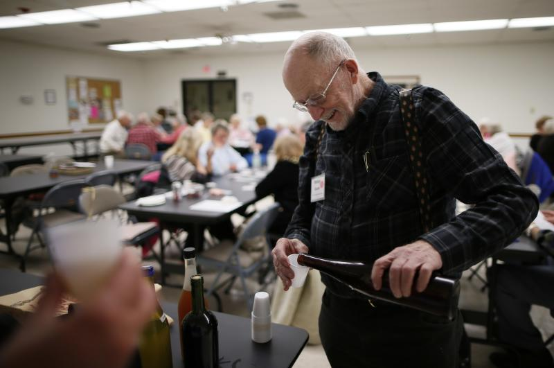 Whitey Sauer, 84, shares out his homemade wine at a singles club in Sun City, Arizona, January 4, 2013. Sun City was built in 1959 by entrepreneur Del Webb as America's first active retirement community for the over-55's. Del Webb predicted that retirees would flock to a community where they were given more than just a house with a rocking chair in which to sit and wait to die. Today's residents keep their minds and bodies active by socializing at over 120 clubs with activities such as square dancing, ceramics, roller skating, computers, cheerleading, racquetball and yoga. There are 38,500 residents in the community with an average age 72.4 years. Picture taken January 4, 2013. REUTERS/Lucy Nicholson (UNITED STATES - Tags: SOCIETY) ATTENTION EDITORS - PICTURE 7 OF 30 FOR PACKAGE 'THE SPORTY SENIORS OF SUN CITY' SEARCH 'SUN CITY' FOR ALL IMAGES