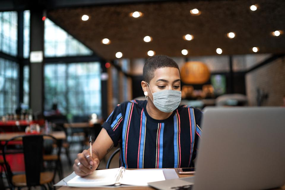 Young woman writing on a notebook while using laptop at restaurant
