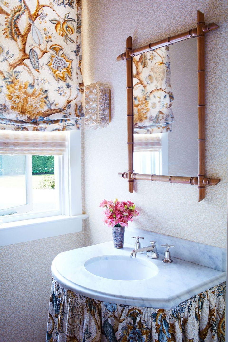 """<p>A skirt on a powder room sink can go a long way to conceal unsightly plumbing and add a serious dose of grandmillennial chic. We love the rust-colored floral that textile designer Remy Renzullo selected for this <a href=""""https://www.elledecor.com/design-decorate/house-interiors/a36501511/remy-renzullo-southampton-ny/"""" rel=""""nofollow noopener"""" target=""""_blank"""" data-ylk=""""slk:Hamptons home."""" class=""""link rapid-noclick-resp"""">Hamptons home.</a> </p>"""