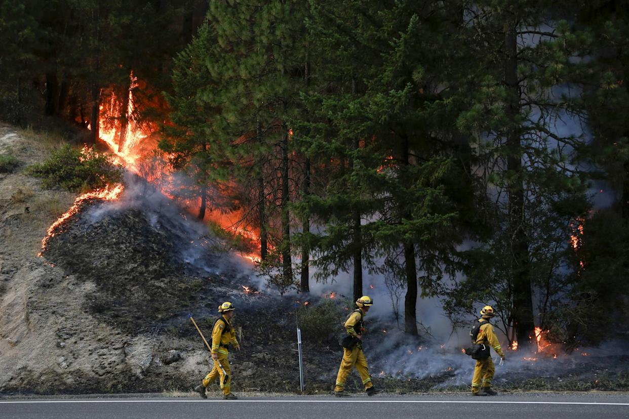 Firefighters monitor flames above State Highway 299 while battling the Carr Fire: Getty