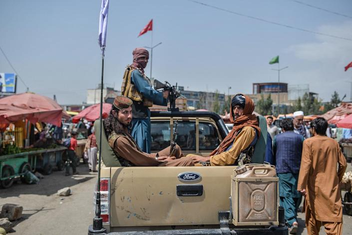 Taliban fighters on a pick-up truck move around a market area, flocked with local Afghan people at the Kote Sangi area of Kabul on August 17, 2021, after Taliban seized control of the capital following the collapse of the Afghan government (AFP via Getty Images)