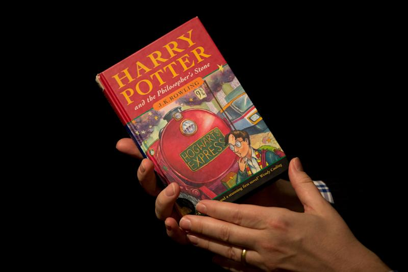 "Sotheby's director of the department of printed books and manuscripts Dr Philip Errington poses for photographers with a first edition copy of the first Harry Potter book ""Harry Potter and the Philosopher's Stone"" containing annotations and illustrations by author J.K. Rowling, during a photocall organized for the media at the auction house's premises in London, Monday, May 20, 2013. The book will be offered for sale as part of the ""First Editions, Second Thoughts"" auction on May 21, for which there are no price estimates available in advance as it is a charity sale. (AP Photo/Matt Dunham)"