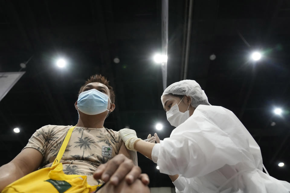 A health worker administers a dose of the AstraZeneca COVID-19 vaccine to a man in Bangkok, Thailand, Friday, Aug. 20, 2021. Thailand has recorded more than 1 million accumulated cases on Friday since the pandemic started in 2020. (AP Photo/Sakchai Lalit)