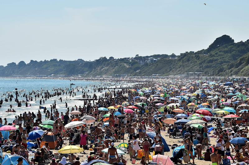 Beachgoers enjoy the sunshine as they sunbathe and play in the sea on Bournemouth beach in Bournemouth, southern England, on June 25, 2020. - Just days after lockdown ended and European travel restrictions were lifted, many were staying home in the cool as a heatwave hit the continent with temperatures touching 40 degrees Celcius. Britain was bracing for a flood of visitors to its beaches with the heatwave expected to last until Friday and temperatures set to climb into the mid-30s in the south and centre of the country. (Photo by Glyn KIRK / AFP) (Photo by GLYN KIRK/AFP via Getty Images)