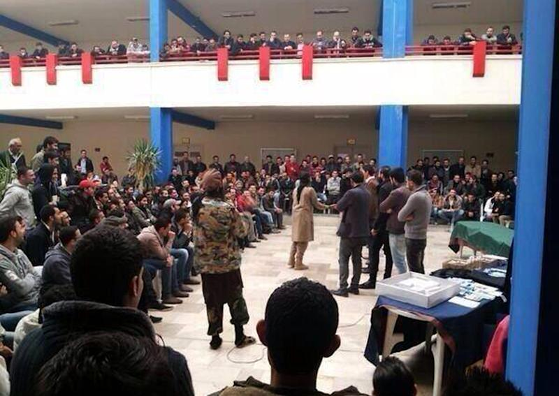 FILE - In this file picture released on Wednesday, Dec. 4, 2013, and posted on the Facebook page of a militant group, members of the al-Qaida affiliated Islamic State of Iraq and the Levant (ISIL) visit with students at a college in the northern city of Raqqa. Once a vibrant, mixed city considered a bastion of support for President Bashar Assad, the eastern city of Raqqa is now a shell of its former life, transformed by al-Qaida militants into the nucleus of the terror group's version of an Islamic caliphate they hope one day to establish in Syria and Iraq. In rare interviews with The Associated Press, residents and activists in Raqqa describe a city where fear prevails, music has been banned, Christians have to pay religious tax in return for protection and face-veiled women and pistol-wielding men in jihadi uniforms patrol the streets. (AP Photo, File)
