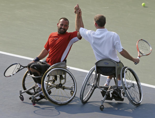 FILE - In this Sept. 9, 2006, file photo, Michael Jeremiasz, of France, left, and Robin Ammerlaan, of the Netherlands, celebrate after defeating Shingo Kunieda, of Japan, and Tadeusz Kruszelnicki, of Poland, in the men's wheelchair doubles final at the U.S. Open Tennis tournament in New York. The U.S. Tennis Association changed its plans and now will include wheelchair competition at the scaled-down U.S. Open after athletes complained about the original decision to drop their event entirely this year. The USTA announced Wednesday, June 24, 2020, that wheelchair tennis will be played at Flushing Meadows from Sept. 10-13, the last four days of the Grand Slam tournament.(AP Photo/Mary Schwalm, File)