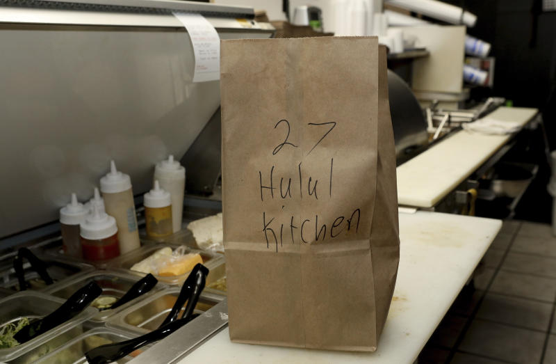 An order from the menu of Halal Kitchen is ready for pickup in a kitchen inside Frato's Pizza in Schaumburg, Ill., on Sept. 6, 2019. Frato's looks like a typical restaurant, but cooks there whip up dishes for four other restaurants at the same time. Thousands of restaurants are experimenting with virtual spin-offs, trying to capitalize on the rising popularity of online ordering. (AP Photo/Teresa Crawford)