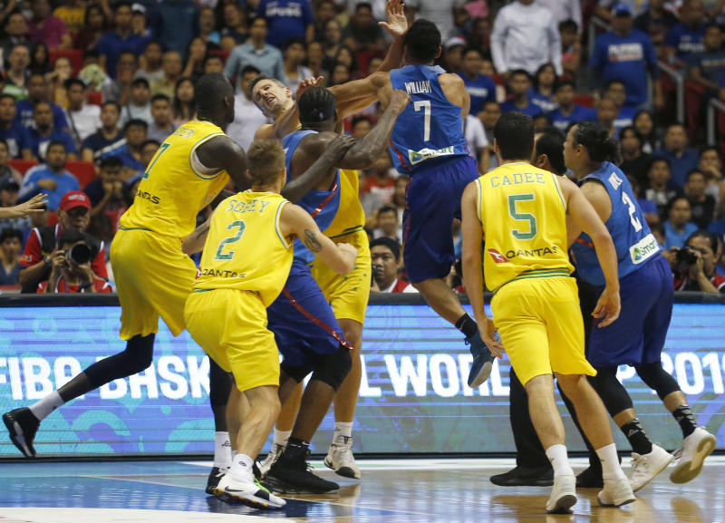 FILE - In this July 2, 2018, file photo, Philippines' Jason William (7) jumps to hit Australia's Daniel Kickert, center left, as others rush to break a brawl during the FIBA World Cup qualifying basketball game at the Philippine Arena in suburban Bocaue township, Bulacan province, north of Manila, Philippines. Kickert was given a five-match ban for unsportsmanlike behavior by international body FIBA on Thursday, July 19, 2018, for his part in a brawl during an Asian qualifier against the Philippines for the 2019 World Cup. (AP Photo/Bullit Marquez, File)