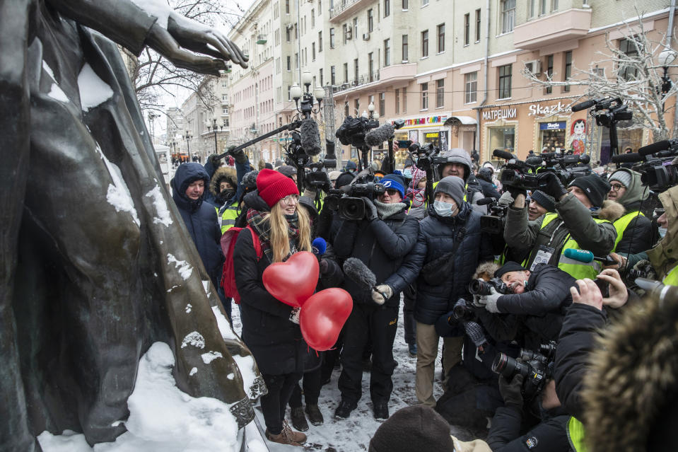 The media gather near a woman at a rally in support of jailed opposition leader Alexei Navalny and his wife Yulia Navalnaya at Arbat street in Moscow, Russia, Sunday, Feb. 14, 2021. The weekend protests in scores of cities last month over Navalny's detention represented the largest outpouring of popular discontent in years and appeared to have rattled the Kremlin. (AP Photo/Pavel Golovkin)