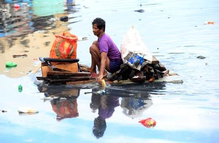 FILE PHOTO: Man uses an improvised banca to collect plastic materials in a polluted river in Manila