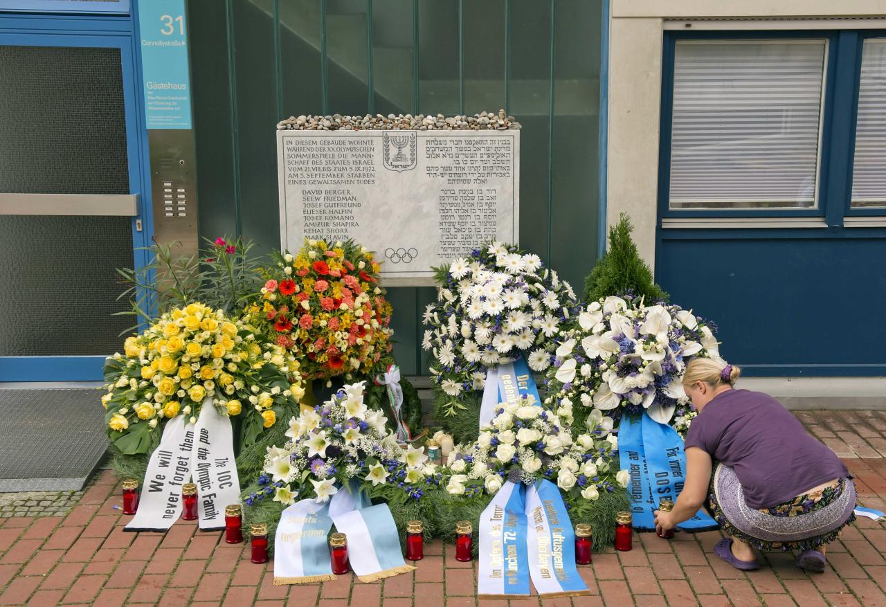 A woman lights candles in front of wreaths at a memorial at the former accommodation building of the Israeli Olympic team in Munich, southern Germany, Wednesday, Sept. 5, 2012, during a commemoration ceremony for the assassination victims of the Olympic games in Munich in 1972. 17 people died in a failed liberation attempt of Israeli hostages, eleven of them of Israel's Olympic team, five terrorists and a German police officer. (AP Photo/dapd, Joerg Koch)