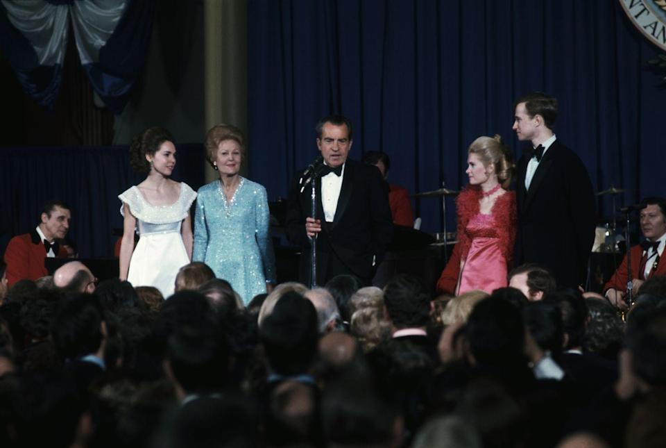 """<p> At the beginning of Richard Nixon's second inaugural ball, the President gathered the First Family and the Vice President's family on stage for photographers, where he shared a few remarks. <a href=""""https://www.smithsonianmag.com/smithsonian-institution/when-was-first-inaugural-ball-180961863/"""" rel=""""nofollow noopener"""" target=""""_blank"""" data-ylk=""""slk:This tradition has continued"""" class=""""link rapid-noclick-resp"""">This tradition has continued</a> in the years since his presidency.</p>"""