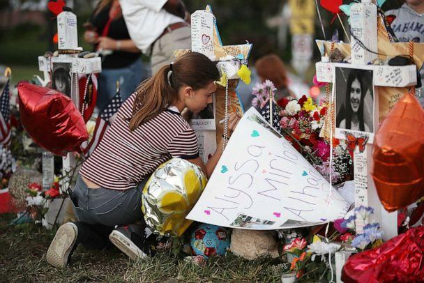 PHOTO: Victoria Seltzer writes a passage on a cross setup in a makeshift memorial in front of Marjory Stoneman Douglas High School in memory of the 17 people that were killed in a mass shooting, Feb. 21, 2018 in Parkland, Fla. (Joe Raedle/Getty Images, FILE)