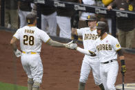 San Diego Padres' Tommy Pham (28) is congratulated by Jake Cronenworth, center, and Austin Nola, right, after hitting a two-run home run during the first inning of a baseball game against the St. Louis Cardinals, Saturday, May 15, 2021, in San Diego. (AP Photo/Denis Poroy)