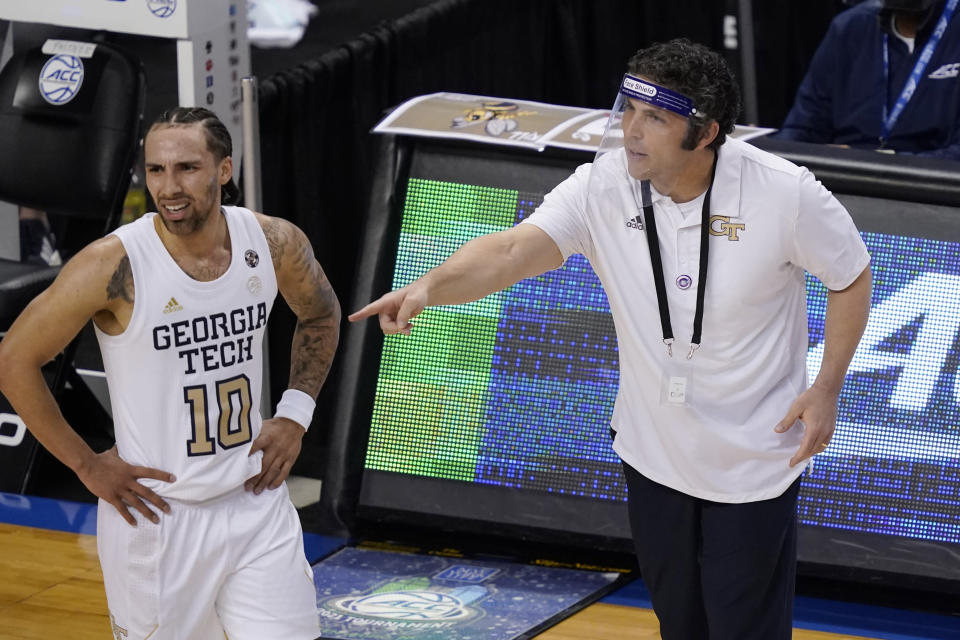 Georgia Tech head coach Josh Pastner talks with guard Jose Alvarado (10) during the first half of an NCAA college basketball game against Miami in the quarterfinal round of the Atlantic Coast Conference tournament in Greensboro, N.C., Thursday, March 11, 2021. (AP Photo/Gerry Broome)