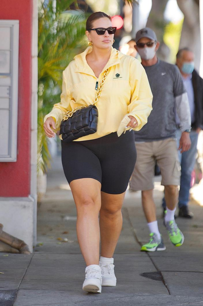 <p>Ashley Graham looks effortlessly gorgeous in a yellow windbreaker and bike shorts on Wednesday in Santa Monica.</p>
