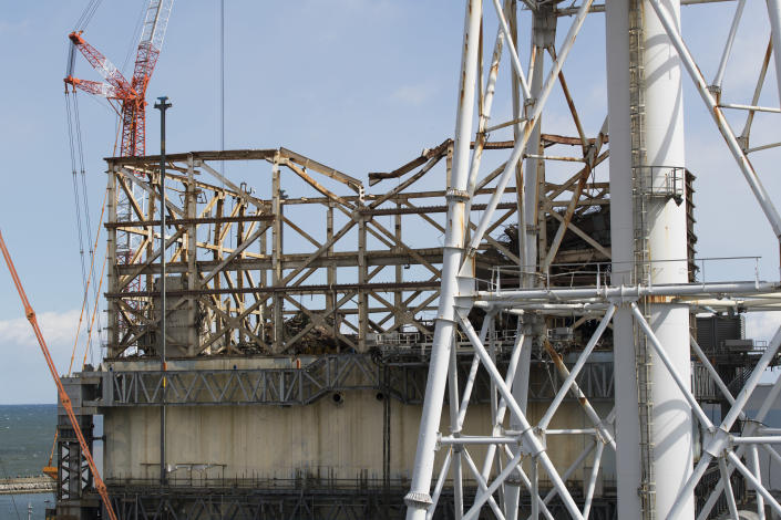 This photo shows the damaged Unit 1 reactor, back, and the exhaust stack shared with the Unit 1 and 2 reactors at the Fukushima Daiichi nuclear power plant in Okuma town, Fukushima prefecture, northeastern Japan, Saturday, Feb. 27, 2021. (AP Photo/Hiro Komae)