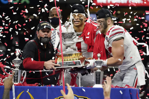 Ohio State head coach Ryan Day, from left, quarterback Justin Fields and linebacker Tuf Borland hold up the trophy after their win against Clemson in the Sugar Bowl NCAA college football game Saturday, Jan. 2, 2021, in New Orleans. Ohio State won 49-28. (AP Photo/John Bazemore)