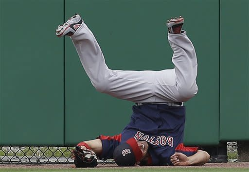 Boston Red Sox center fielder Shane Victorino flips over after catching Ryan Howard's second-inning flyout at the outfield wall in a spring training baseball game against the Philadelphia Phillies in Clearwater, Fla., Sunday, March 24, 2013. (AP Photo/Kathy Willens)