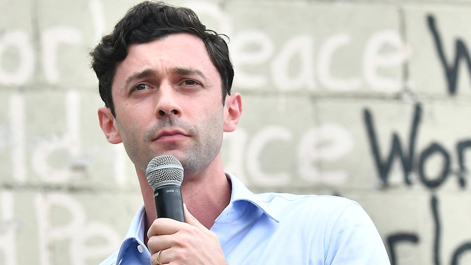 Jon Ossoff holding a microphone
