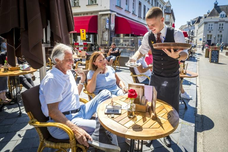 People sit at a cafe's terrace in Maastricht, the Netherlands on Monday as the country eases lockdown measures