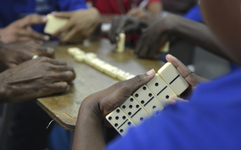 """In this Oct. 31, 2013 photo, vocational students learn domino strategies in a classroom in Kingston, Jamaica. A government program is teaching domino strategies to inner-city young adults from gang-steeped areas. Under the guidance of a Justice Ministry officer who devised the """"Dominoes for Life"""" program, participants say the game is helping them work through possible outcomes and develop thinking skills as they learn how to better connect the dots in the real world. (AP Photo/David McFadden)"""