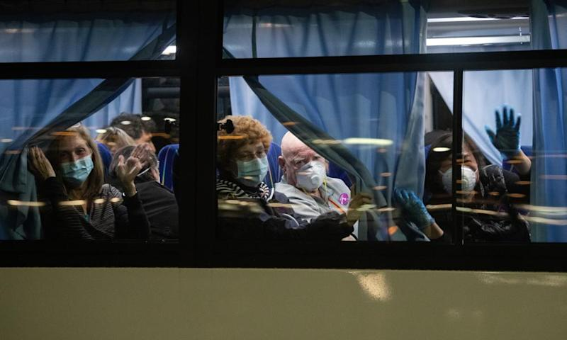 US citizens wave from a bus as they leave cruise ship to be repatriated