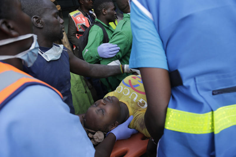 Rescue workers carry a person rescued from the rubble of a building that collapsed in Tasia Embakasi, an east neighbourhood of Nairobi, Kenya on Friday Dec. 6, 2019. A six-story building collapsed in Kenya's capital on Friday, officials said, with people feared to be trapped in the debris. Police say people have been rescued by residents using their bare hands. (AP Photo/Khalil Senosi)