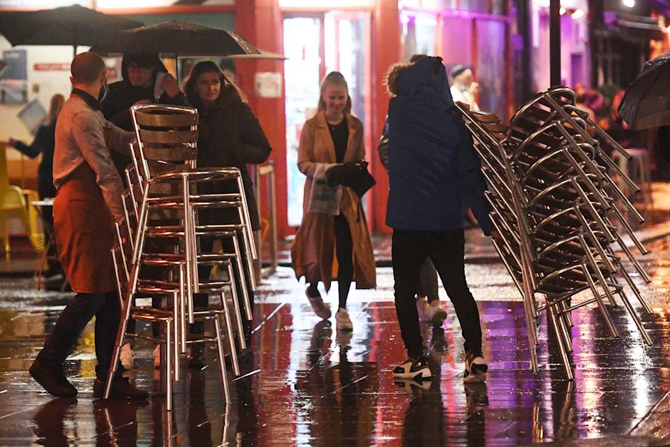 Workers pack away chairs outside a bar in Soho, London, ahead of the 10pm curfew pubs and restaurants are subject to in order to combat the rise in coronavirus cases in England.