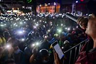 Pro-democracy protesters hold up their mobile phones flashlights as they listen to a speaker during a rally at Bangkok's Victory Monument