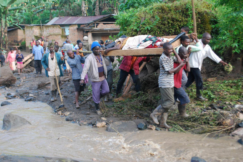 Residence carry an injured person in Bududa District, Uganda, Friday, Oct. 12, 2018. At least 30 people died in mudslides triggered by torrential rains in a mountainous area of eastern Uganda that is prone to such disasters, a Red Cross official said Friday. More victims were likely to be discovered when rescue teams access all the affected areas in the foothills of Mount Elgon, said Red Cross spokeswoman Irene Nakasiita. (AP Photo/ Ronald Kabuubi)