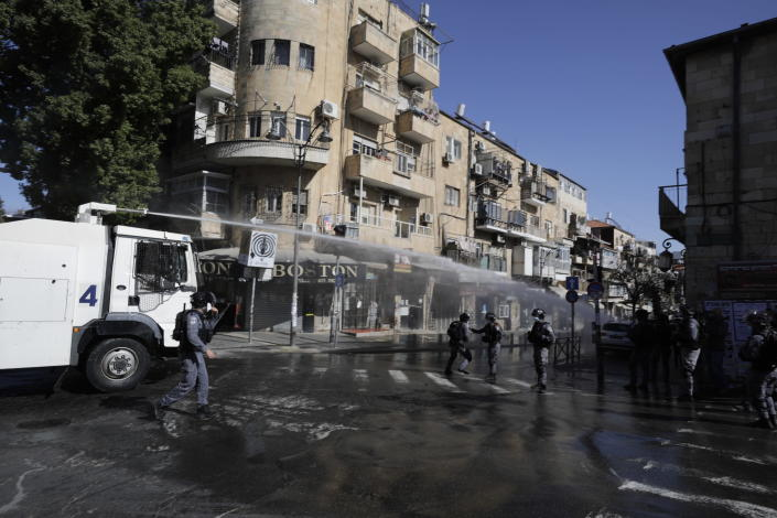 Israeli police shoot a water canon towards protesters in an ultra-orthodox neighborhood of Jerusalem, Sunday, Jan. 24, 2021. Ultra-Orthodox demonstrators clashed with Israeli police officers dispatched to close schools in Jerusalem and Ashdod that had opened in violation of health regulations on Sunday. (AP Photo/Sebastian Scheiner)