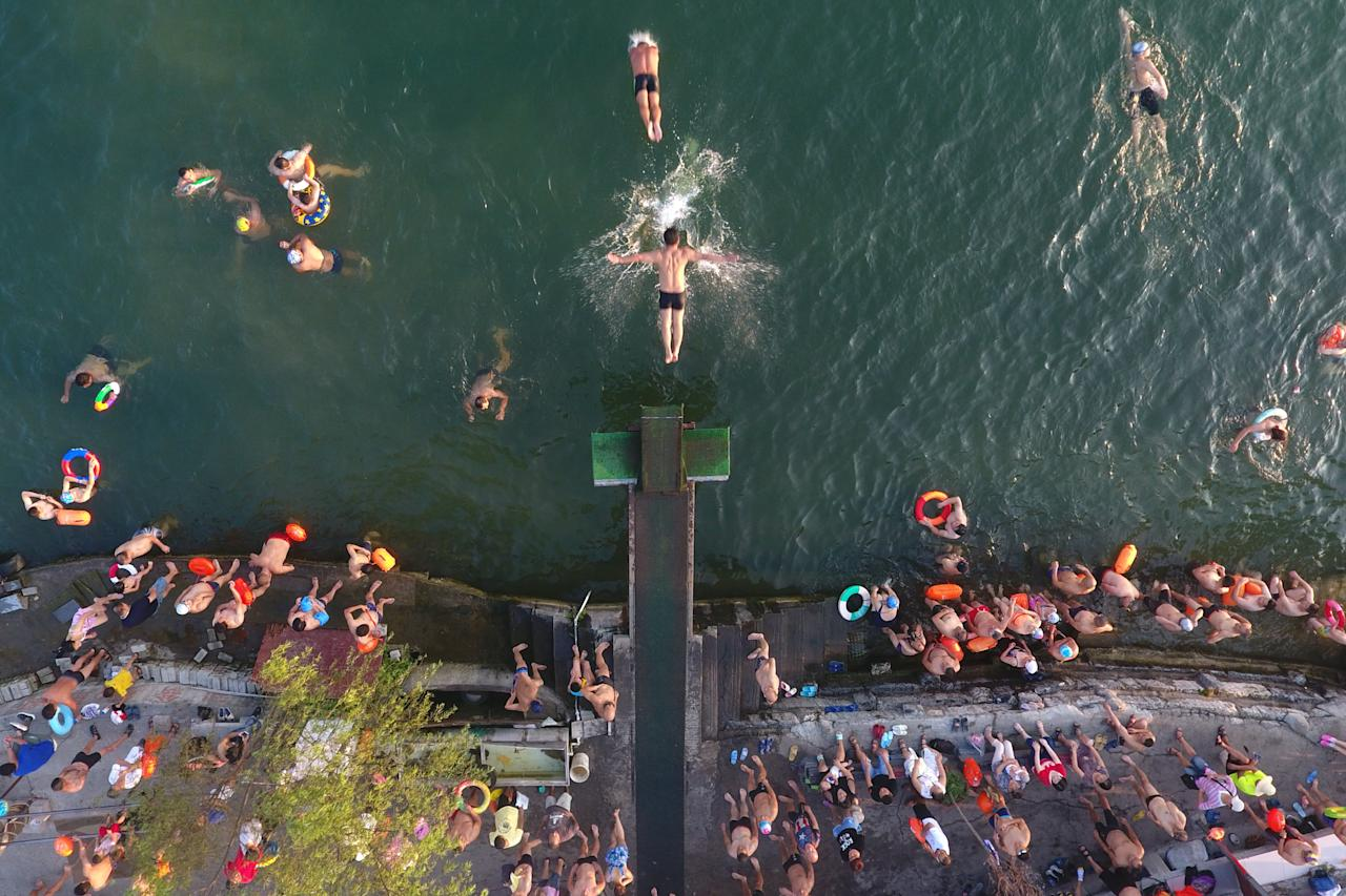 <p>People swim in the Han River to cool off as a heat wave hits the area in Xiangyang, Hubei Province of China. (VCG) </p>